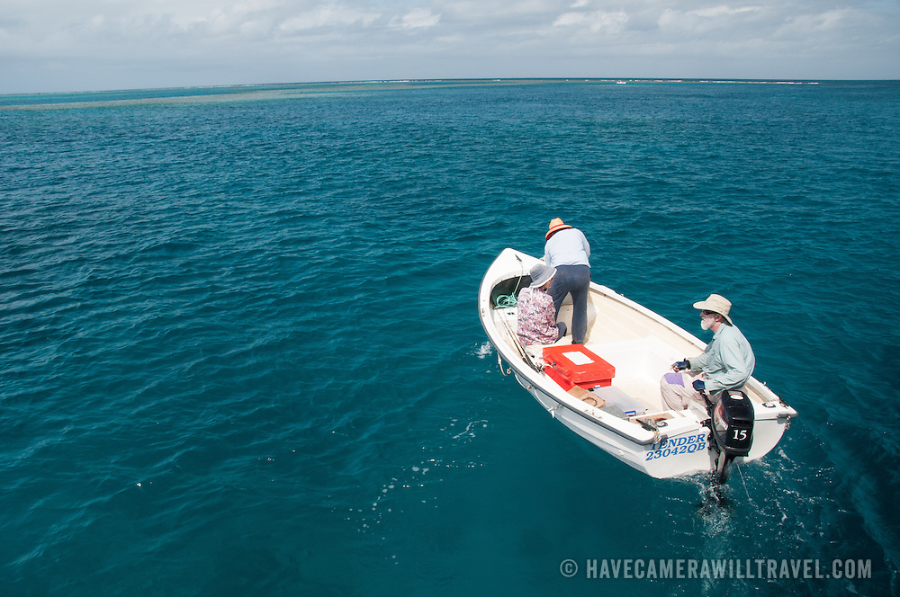 A small boat with three people heads out fishing on flat seas on Australia's Great Barrier Reef.