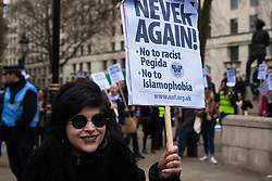 Whitehall, London, April 4th 2015. As PEGIDA UK holds a poorly attended rally on Whitehall, scores of police are called in to contain counter protesters from various London anti-fascist movements. PICTURED: A counter protester with her banner shows that whilst there are a few ongoing scuffles between anti-fascists and police, spirits remain high.