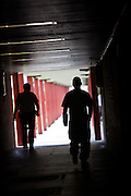 A prisoner and prison officer walking between buildings. HMP The Mount, Bovingdon, Hertfordshire
