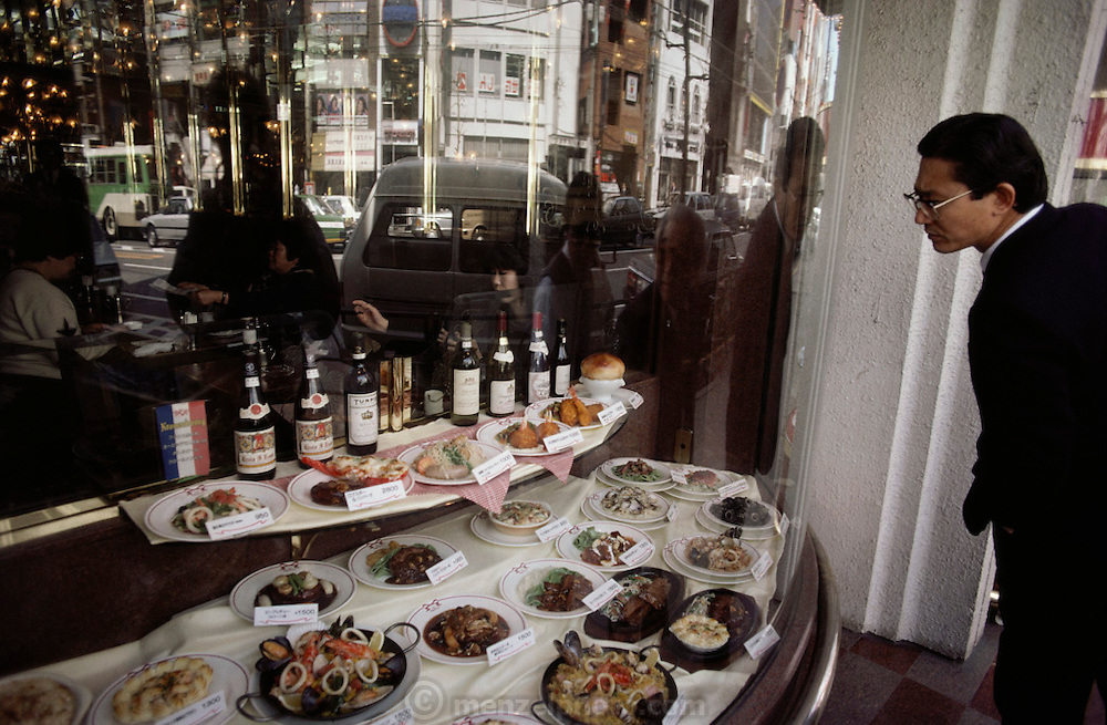 A potential diner examines samples of plastic food in a restaurant window in Tokyo, Japan.