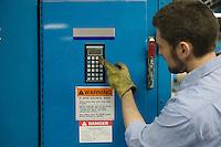 Man pressing keypad in newspaper factory