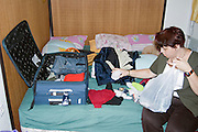Woman Packing for a trip articles and suitcase on a bed in total disorder Model Release available