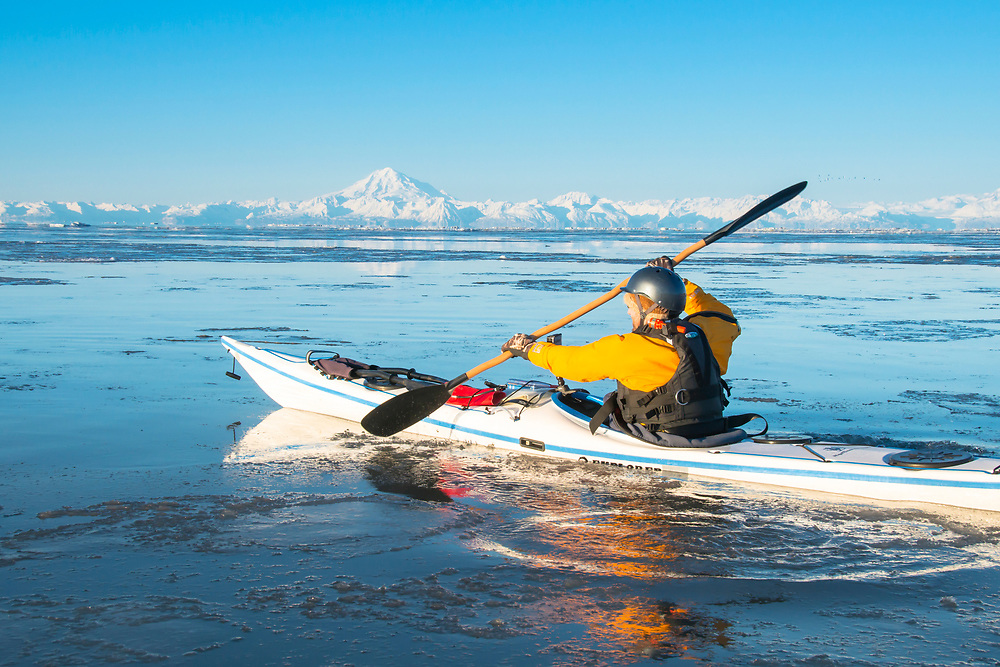A man paddles among the ice flows of Cook Inlet with Mt. Redoubt in the background. M.R.