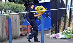 © London News Pictures. 29/07/2013. Manchester, UK. A police officer laying flowers for a member of the public at  the scene on Delta Walk, in Moston, Manchester where A father has been stabbed to death and his 13-year-old child left in a critical condition. A second man, who also suffered stab wounds,  died after he crashed a hijacked car into a nearby pub. Photo credit Steve Allen/LNP