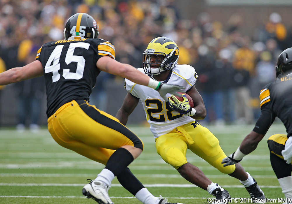 November 05, 2011: Michigan Wolverines running back Fitzgerald Toussaint (28) tries to avoid Iowa Hawkeyes linebacker Tyler Nielsen (45) and Iowa Hawkeyes defensive back Jordan Bernstine (4) during the first quarter of the NCAA football game between the Michigan Wolverines and the Iowa Hawkeyes at Kinnick Stadium in Iowa City, Iowa on Saturday, November 5, 2011. Iowa defeated Michigan 24-16.