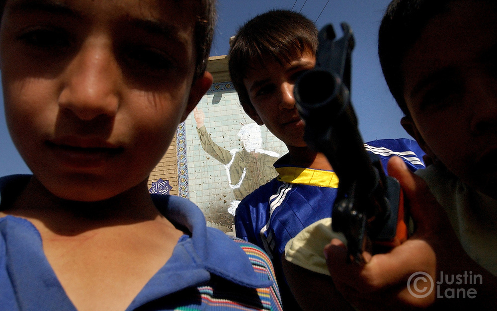 Three young boys play with a toy gun in front of a defaced monument to Saddam Hussein.