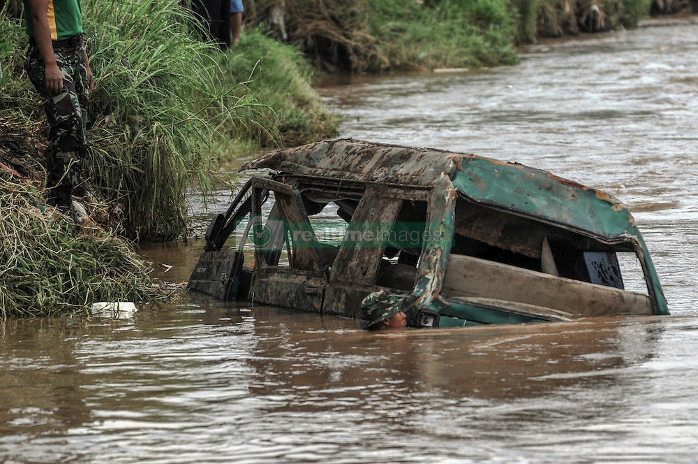 September 23, 2016 - Garut, Indonesia - Soldiers of the Army Strategic Reserve Commandsearch for victims of the flood disaster in a car which was found drifting on the river in Cimacan, Garut, on September, 23.2016. The death toll from devastating floods and landslides in Indonesia has risen to 26, an official said, with hopes fading for 19 others still missing. (Credit Image: © Dasril Roszandi/NurPhoto via ZUMA Press)