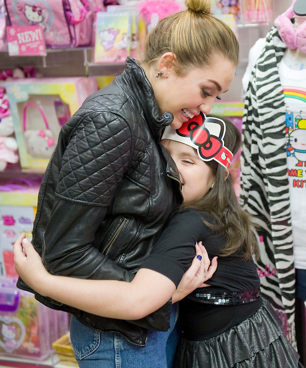 "Miley Cyrus gets a big hug from Jadzia Acosta, 8, who came with her mother from Miami to meet Cyrus at the Sanrio Store in South Coast Plaza as part of a Make A Wish Foundation's wish-granting. Jadzia had earlier squealed with delight upon meeting the life-sized Hello Kitty mascot in the store, but Miley? ""I felt happy,"" she said, and then, after thinking about it a little more, added: ""A lot, a lot, a lot!"""