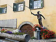 "A metal sculpture of a man cracks a whip in front of an old Chesa Planta in the main town square of Zuoz, one of the best preserved villages in Upper Engadine. Visit Graubünden canton in Switzerland, the Alps, Europe. The Swiss valley of Engadine translates as the ""garden of the En (or Inn) River"" (Engadin in German, Engiadina in Romansh, Engadina in Italian)."