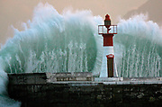 A massive wave breaks over Kalk Bay harbour wall in Cape Town, South Africa.