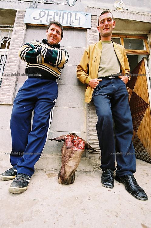 Zwei Armenier stehen vor einer Metzgerei der südarmenischen Stadt Sissian. Auf dem Boden zwischen ihnen der Kopf einer eben geschlachteten Kuh. Armenian butchers with a cows head in front of their shop in a rural village.