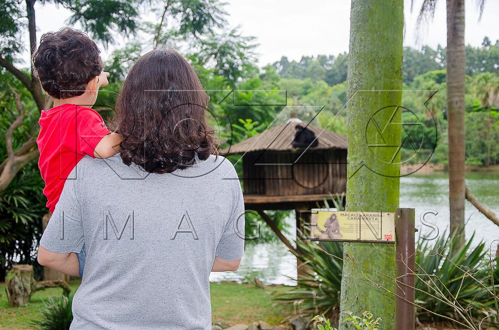 Criança no colo de mulher observando macacos na Fundação Parque Zoológico de São Paulo, São Paulo - SP, 02/2016. Uso de imagem autorizado.