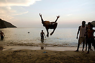 A group of young Colombians practice their gymnastics moves at the beach in Taganga, Colombia