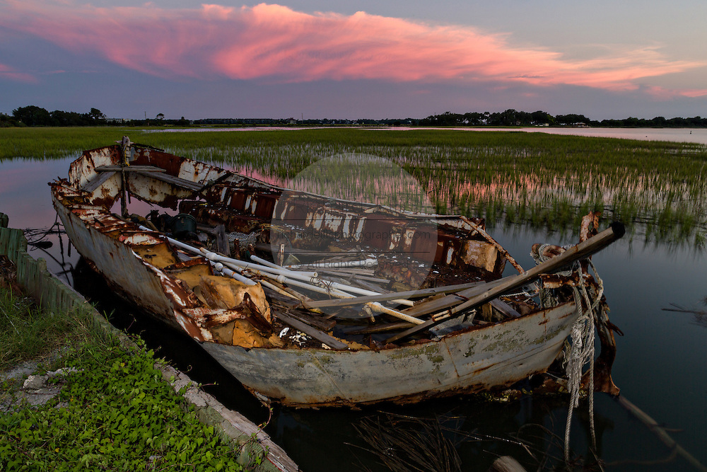A wrecked boat along the marsh at sunset in Folly Beach, SC.