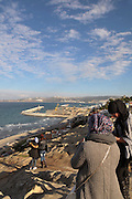 Some girls take pictures on the cliffs facing the Atlantic Ocean just outside the Hafa Cafe