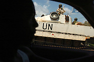 A taxi driver passes an armored United Nations unit on patrol in downtown Monrovia. UN troops have helped keep the peace in Liberia since 2003.