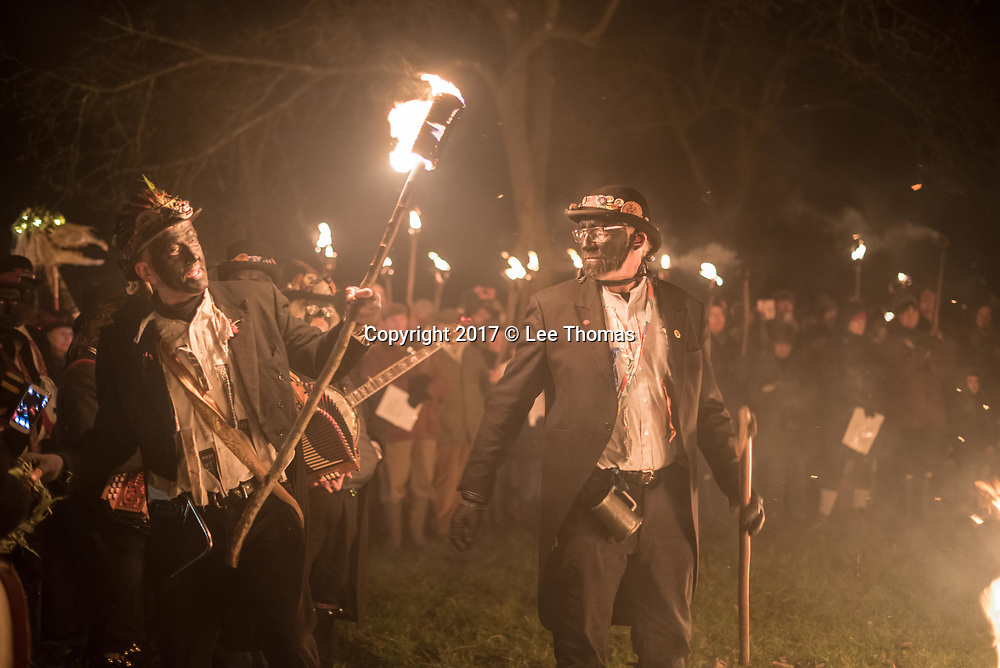 Much Marcle, Herefordshire, UK. 6th January 2018. Pictured:  Morris men perform their wassail rituals in the cider orchard. / Hundreds of people both young and old gathered at the Westons Cider Mill and adjoining orchard to take part in the traditional Wassail ceremony. The event at Much Marcle in Herefordshire was attended by the Silurian morris side who entertained the crowd with witty repartee, raucous dancing and music. According to their website, the true origins of blackened faces are lost to history, but are widely believed to be simply a form of disguise, possibly to overcome the oppressive anti-begging laws of the 17th century, and the eternal embarrassment of being a morris man. The orchard-visiting wassail refers to the ancient custom of visiting orchards in cider-producing regions of England, reciting incantations and singing to the trees to promote a good harvest for the coming year.     // Lee Thomas, Tel. 07784142973. Email: leepthomas@gmail.com  www.leept.co.uk (0000635435)