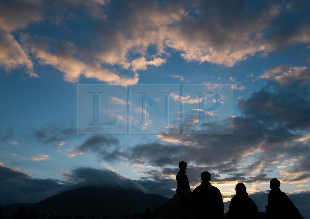 © Licensed to London News Pictures. <br /> 21/06/2014. <br /> <br /> Castlerigg Stone circle, Cumbria, England<br /> <br /> Visitors to the ancient site of Castlerigg Stone Circle near Keswick in Cumbria celebrate the sunrise on the morning of the Summer Solstice.<br /> <br /> Photo credit : Ian Forsyth/LNP
