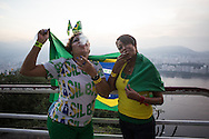 Brazil fans Maria Cristina Ribiero (L) and Sueli Ribiero (R) look on from the top of the Morro da Urca mountain which is the staging point halfway up to the top of Sugarloaf. The whole of the mountain was closed for a private party with thousands of people watching the Brazil v Mexico 0-0 draw on big screens then partying afterwards. Picture by Andrew Tobin/Focus Images Ltd +44 7710 761829<br /> 17/06/2014
