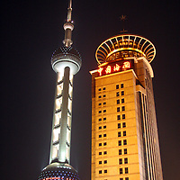 Asia, China; Shanghai. The Oriental Pearl Tower contrasts with another modern skyscraper in Shanghai's Pudong.
