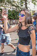 A woman films herself as she walks around - Crowds flock to see the 50th Notting hill carnival on Bank Holiday Monday.