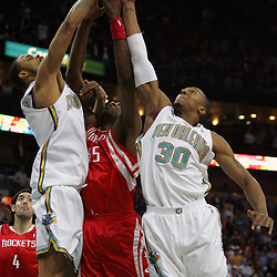 New Orleans Hornets defenders Tyson Chandler (L) and David West (R) jump for a rebound with Houston Rockets center Dikembe Mutombo in first quarter of their NBA game on March 19, 2008 at the New Orleans Arena in New Orleans, Louisiana.