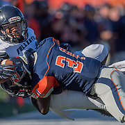Costa Mesa, CA - Orange Coast College defensive back Kyre Adams (31) tackles Fullerton College wide receiver Daurice Simpson (left). Fullerton went on to win the November 5th game, 35-14.