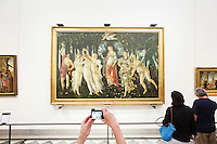 "FLORENCE, ITALY - 29 JUNE 2016: Visitors photograph and look at the ""Birth of Venus"" (1484) by Sandro Botticelli, in the Botticelli room of the Uffizi Gallery in Florence, Italy, on June 29th 2016.<br /> <br /> Art historian Eike Schmidt, former curator and head of the Department of Sculpture, Applied Art and Textiles at the Minneapolis Institute of Arts, became the first non-Italian director of the Uffizi in August 2015, replacing Antonio Natali who directed the gallery for 9 years. One of the main goals of the new director is to open the Vasari Corridor to the general public. Currently the corridor can only be visited with group reservations made by external tour and travel agencies throughout the year.<br /> <br /> The Vasari Corridor is is a 1-kilometer-long (more than half mile) elevated enclosed passageway which connects the Palazzo Vecchio with the Palazzo Pitti, passing through the Uffizi Gallery and crossing the Ponte Vecchio above the Arno River, in Florence. The passageway was designed and built in 1564 by Giorgio Vasari in only 6 months to allow Cosimo de' Medici and other Florentine elite to walk safely through the city, from the seat of power in Palazzo Vecchio to their private residence, Palazzo Pitti. The passageway contains over 1000 paintings, dating from the 17th and 18th centuries, including the largest and very important collection of self-portraits by some of the most famous masters of painting from the 16th to the 20th century, including Filippo Lippi, Rembrandt, Velazquez, Delacroix and Ensor."
