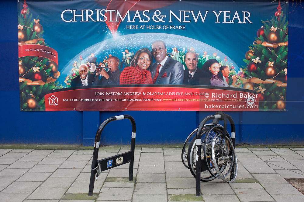A banner for the black church House of Praise with abandoned and locked bicycle wheels in Walworth, south London.