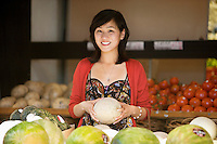 Portrait of smiling young woman holding melon in market