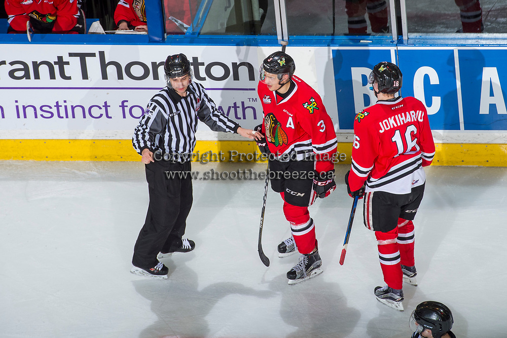 KELOWNA, CANADA - APRIL 8: Linesman Ron Dietterle stands on the ice in front of Caleb Jones #3 and Henri Jokiharju #16 of the Portland Winterhawks against the Kelowna Rockets on April 8, 2017 at Prospera Place in Kelowna, British Columbia, Canada.  (Photo by Marissa Baecker/Shoot the Breeze)  *** Local Caption ***