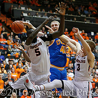 Oregon State's Cheikh (cq) N'diaye (cq), left, and Tres Tinkle, right, fights UCLA's Thomas Welsh for a loose ball in the second half of an NCAA college basketball game in Corvallis, Ore., on Wednesday, Jan. 20, 2016. UCLA won 82-73. (AP Photo/Timothy J. Gonzalez)