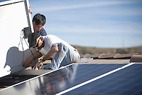 Two people on a rooftop working on solar panelling