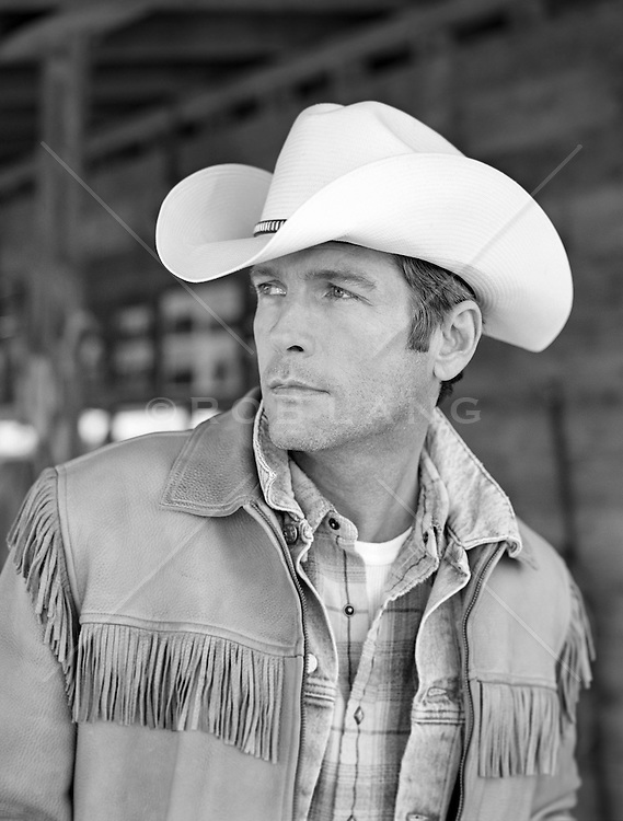 portrait of a handsome All American cowboy in a fringe jacket and cowboy hat