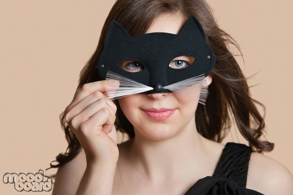 Portrait of a young woman looking through eye mask over colored background