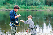Alaska. Fairbanks. A father and son fishing catch/release for grayling on the Upper Chena River. MR.