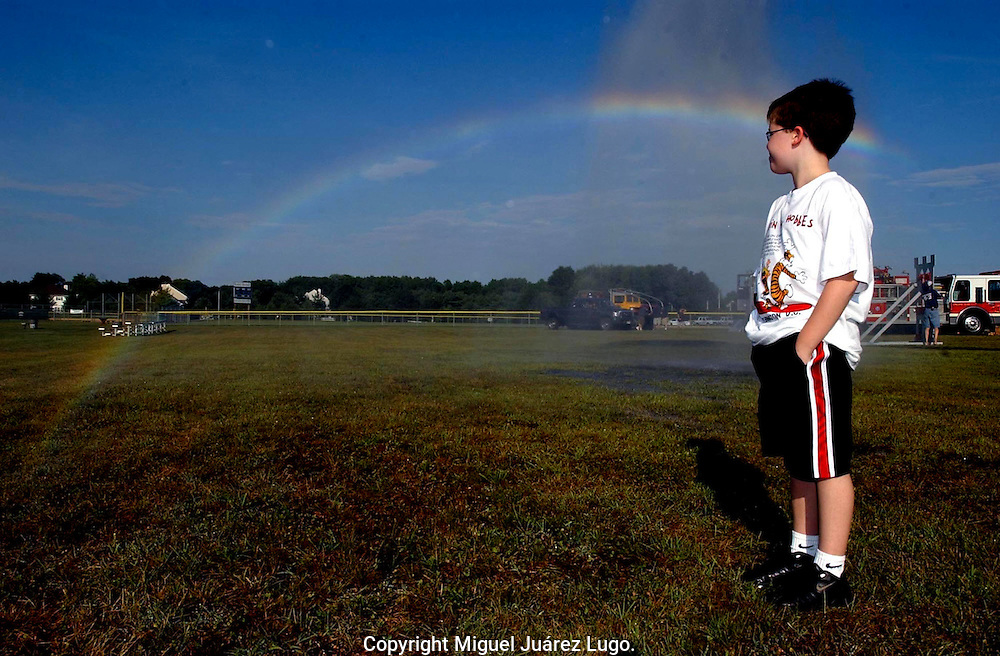 TINTON FALLS NJ - DJ Martin, 11, makes a pause to contemplate a rainbow created the spray water from a Fire Department ladder truck to cool off peasants during the Community Day held at the Ranney School. (Photo by Miguel Juárez Lugo)
