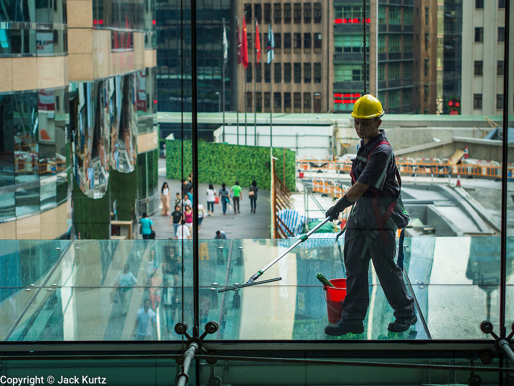 10 AUGUST 2013 - HONG KONG: A window washer works in the ifc (International Financial Centre) mall in Hong Kong. Hong Kong is one of the two Special Administrative Regions of the People's Republic of China, Macau is the other. It is situated on China's south coast and, enclosed by the Pearl River Delta and South China Sea, it is known for its skyline and deep natural harbour. Hong Kong is one of the most densely populated areas in the world, the  population is 93.6% ethnic Chinese and 6.4% from other groups. The Han Chinese majority originate mainly from the cities of Guangzhou and Taishan in the neighbouring Guangdong province.      PHOTO BY JACK KURTZ