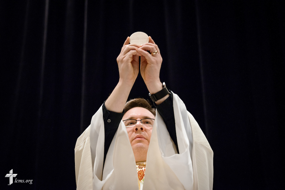 The Rev. Christopher Esget, LCMS sixth vice-president and pastor of Immanuel Evangelical-Lutheran Church, Alexandria, Va., consecrates the elements during the Lord's Supper on Friday, Jan. 27, 2017, in Arlington, Va. LCMS Communications/Erik M. Lunsford