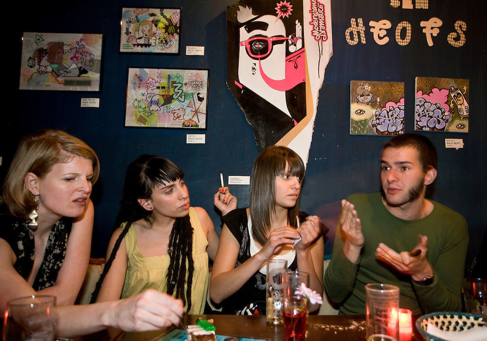 "11:22 PM: A group of young people in their mid-twenties enjoy a tapas dinner at ""Carajillo"", in anticipation to a night clubbing in Madrid."