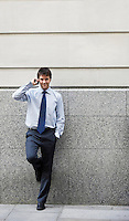 Businessman on cell phone leaning on wall of building