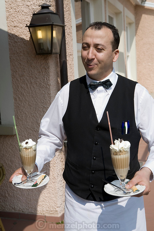 A waiter carrying two desserts at a restaurant on the Moselle River, overlooking the French border with. Luxembourg.