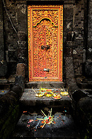 Balinese Temple Offerings: Offerings of incense, flowers and food litter the stairway leading to the ornate, locked front door of the Hindu Temple in Padangbai Bali, Indonesia.