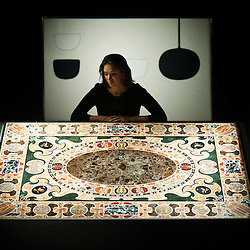 London,UK - 7 June 2013: A Sotheby's employee named Rosie leans to look a magnificient Late Renaissance Antique Marble Inlaid Table top (Est. £800.000-1.200.000) during the preview of this summer auction estimated at £100 million.