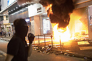 HONG KONG: Sunday 20 October 2019 A masked anti-government protester watches on as the entrance to Chinese mobile phone store Xiaomi burns on Sunday in Hong Kong. Hundreds of thousands of protesters marched through the city's streets in defiance of the march being denied permission to take place as demonstrations roll into a 14th week. <br /> Rick Findler / Story Picture Agency