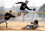 Mitchell shortstop Drew Kitchens fields a throw to second base while leaping over Harrisburg's Sam Menke who successfully steals second as Mitchell's Calvin Hegg backs up Kitchens on the play during the first game of a doubleheader on Wednesday at Drake Field. (Matt Gade / Republic)