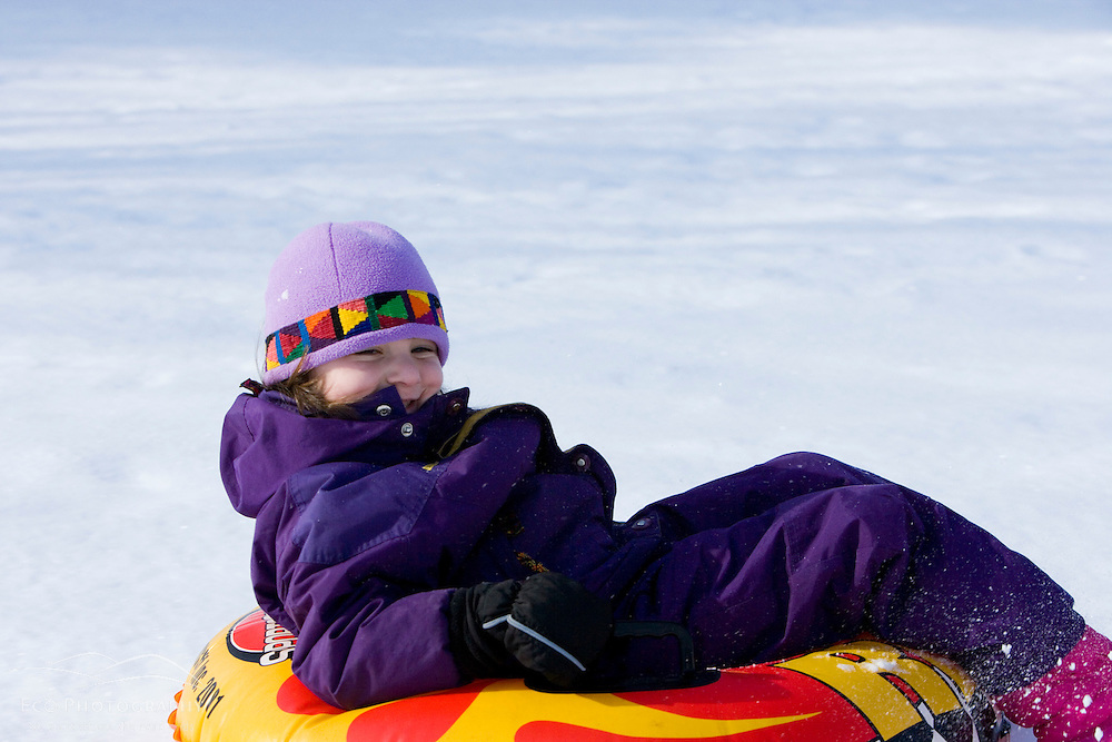 A young girl (age 6) rides her snow tube down a  hill in Quechee, Vermont.