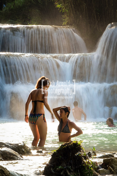 Travellers cooling off in the turqoise waters of Kuang Si Waterfalls near Luang Prabang, Laos.