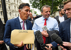 "© Licensed to London News Pictures. 12/06/2018. London, UK.   Leave.EU founder ARRON BANKS and Leave.EU campaigner ANDY WIGMORE hold a ""TOP SECRET"" envelope as they arrive at Portcullis House in London where they are due to give evidence to a Commons Digital, Culture, Media and Sport Committee about fake news. The pair have been accused of collusion with Russian officials around the time of the Brexit referendum. Photo credit: Ben Cawthra/LNP"
