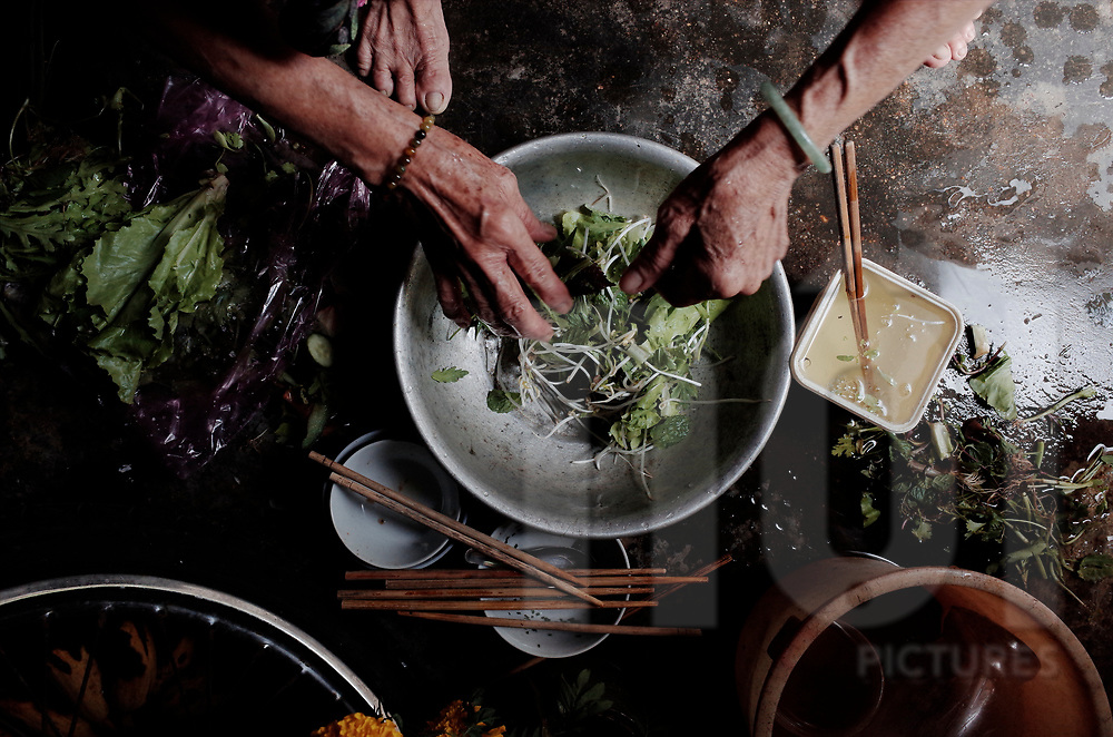 Top view of hands mixing herbes in a bowl, Vietnam, Southeast Asia
